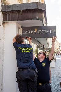 Feuerwehr demontiert ein beschädigtes Werbeschild