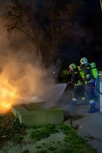 Passanten entfernen mehrer Mülltonnen von einer brennenden Müllinsel
