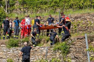 Person abgestürzt - Feuerwehrkräfte tragen Mann einen Weinberg hinunter