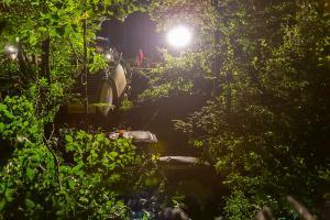 Traktor mit Heuballenpresse stürzt von einem Forstweg in den Wald