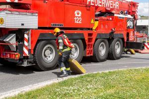 Unimog stürzt in einem Kreisverkehr um und durchbricht eine Lärmschutzwand